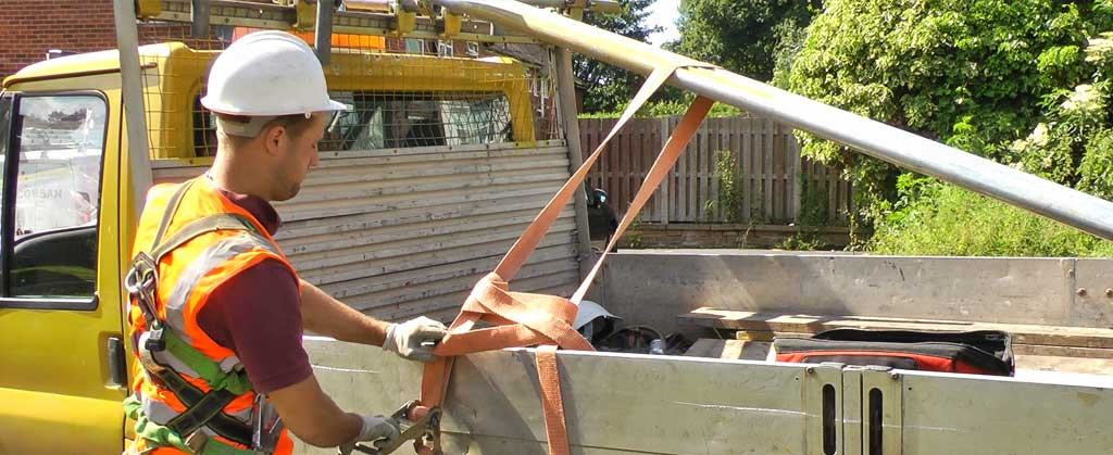 close up side view of a brooks scaffolder loading scaffolding onto their gold coloured truck